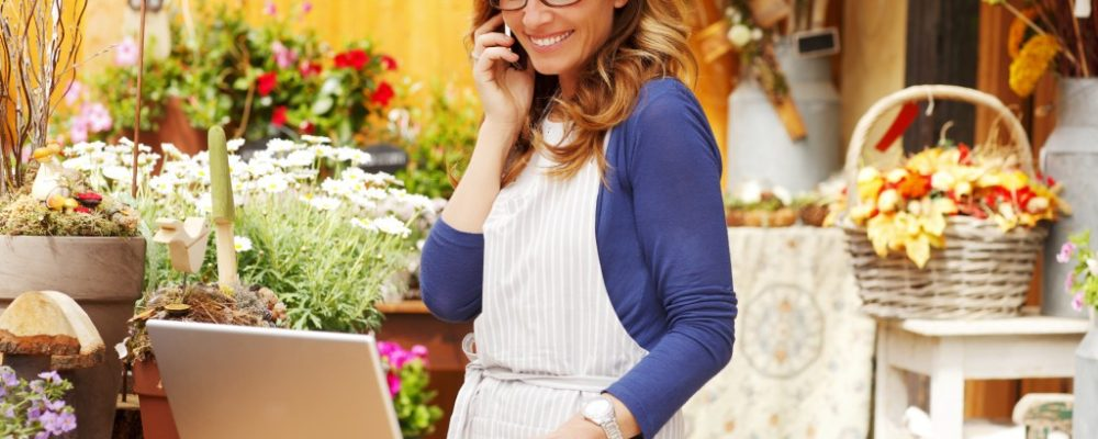 Flower shop owner using her laptop and phone