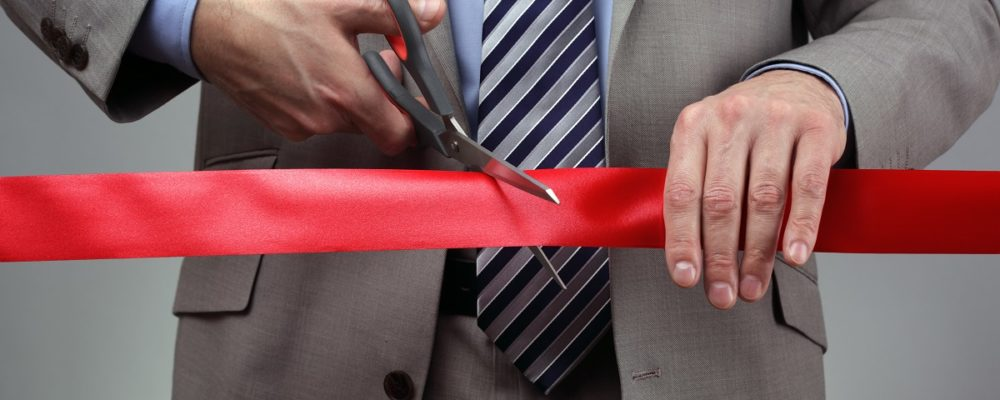 Man cutting a ribbon for his new venture