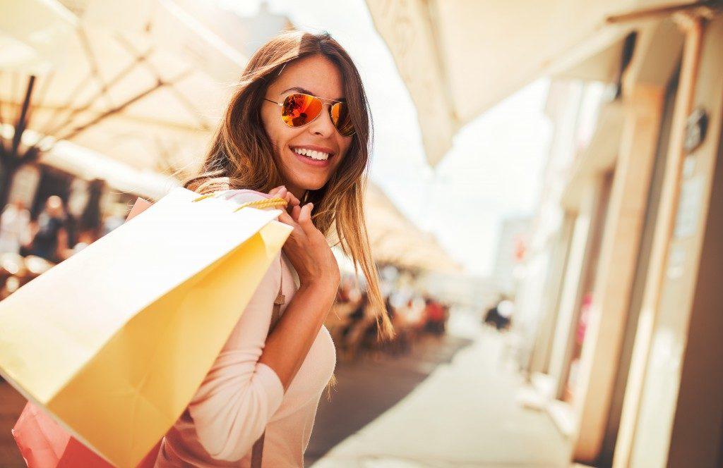 Happy woman with shopping bags enjoying in shopping