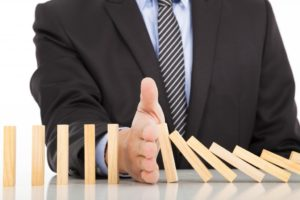 Businessman hand stopping domino