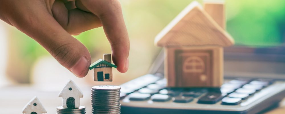 Tiny house model on stack of coins mortgage concept