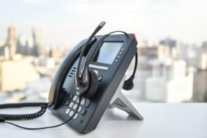 Phone with headset beside the window