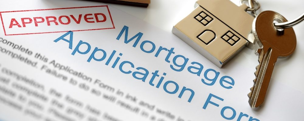Approved mortgage loan application with stamp and house key