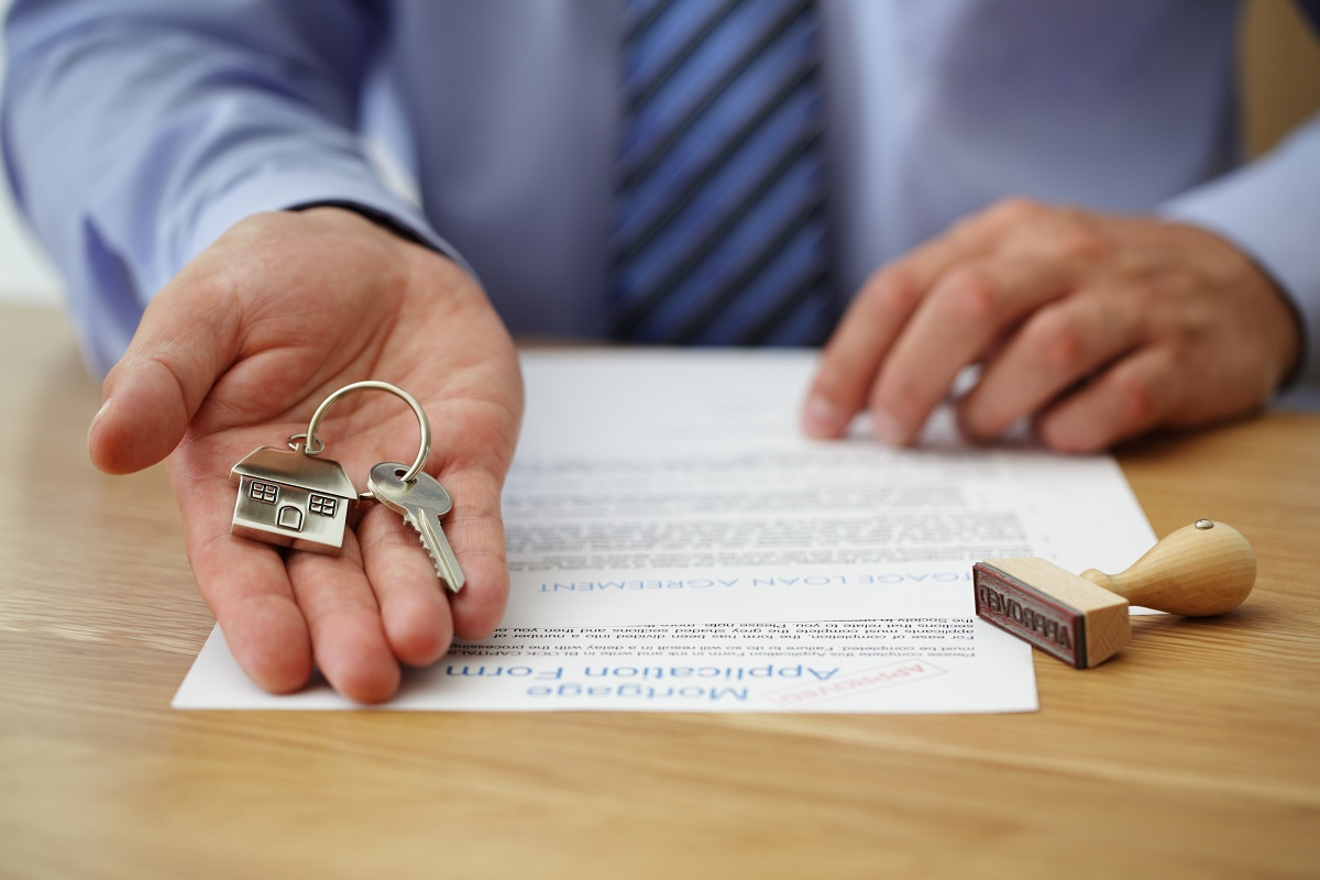 House keys being handed with home loan form