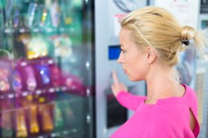Woman choosing what to buy in the vending machine