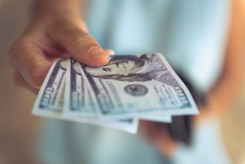 Holding dollar bills