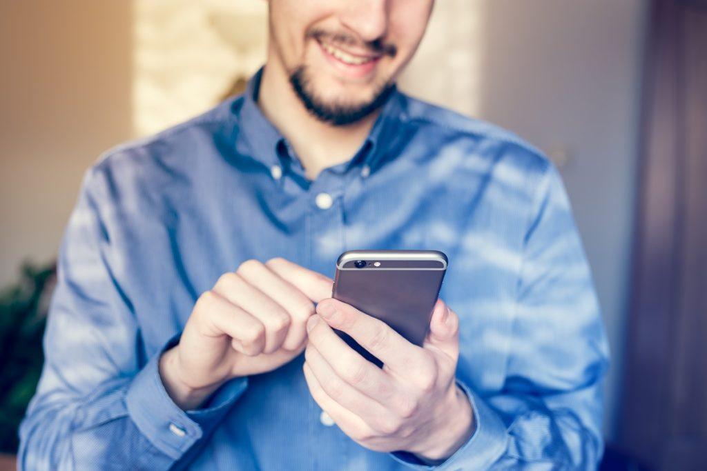 man scrolling through his phone