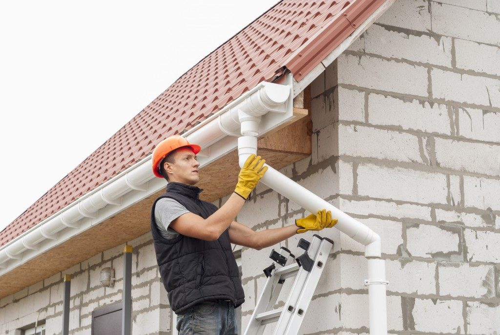 man repairing a downspout