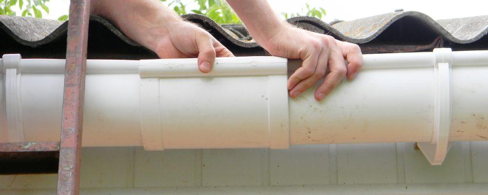 man repairing a home's gutter