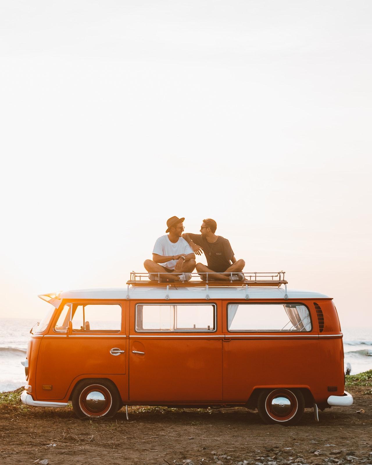 2 men talking on top of a volkswagen bus