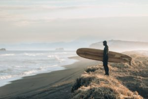 man holding surfboard looking at the ocean