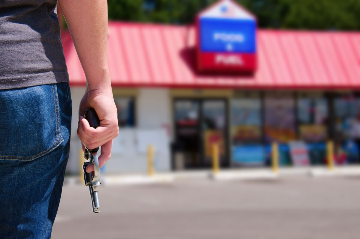 man holding gun walking to convenience store
