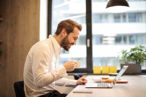 man smiling at his computer