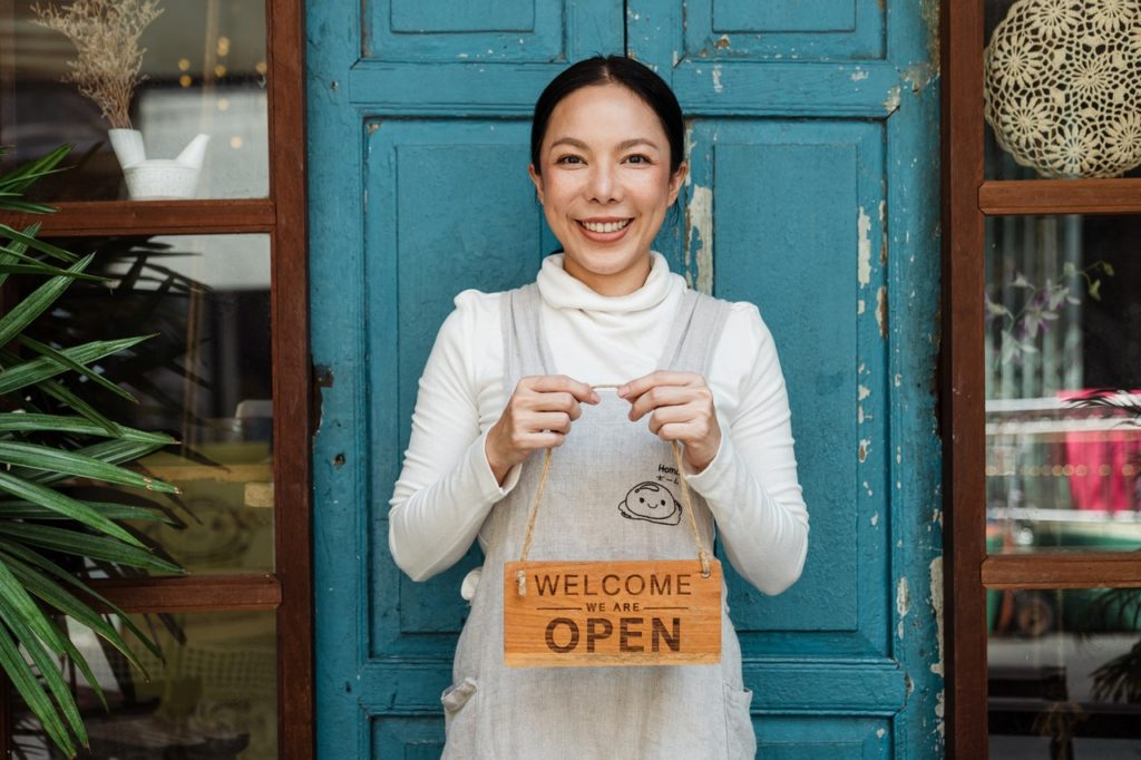woman holding come in we're open sign