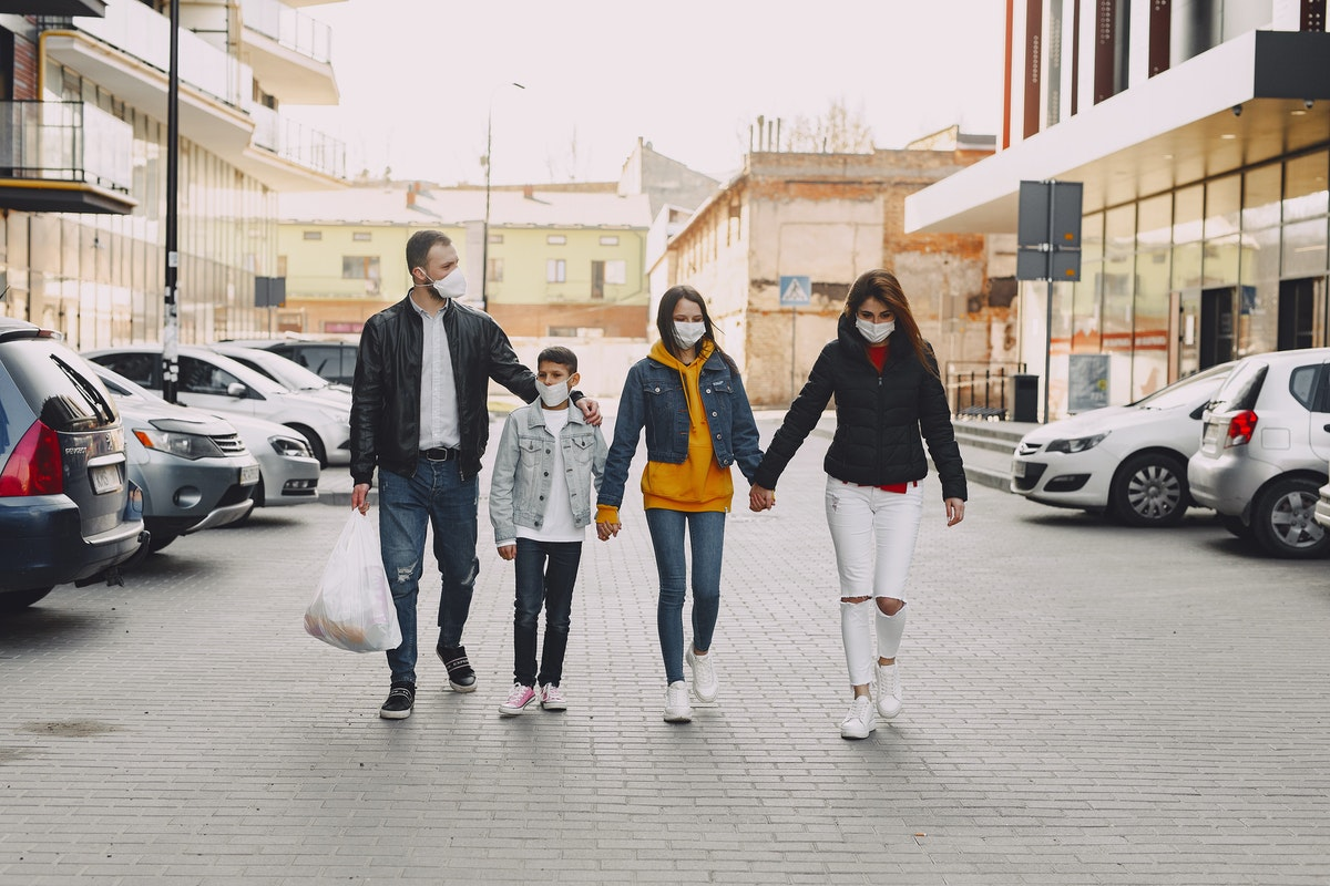 family walking holding hands wearing facemask
