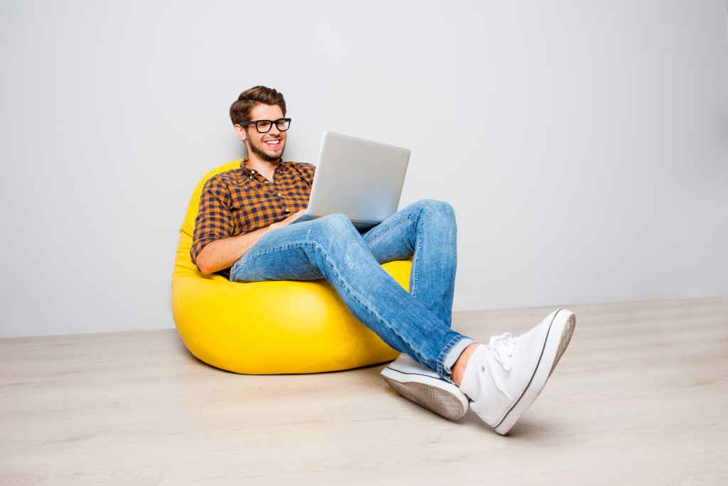 a guy doing work on his computer while smiling