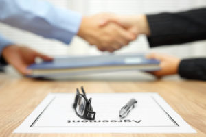 men shaking hands after signing an agreement